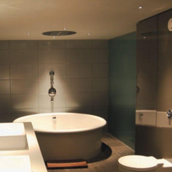 Recessed LED downlights lighting up bath tub in tiled bathroom