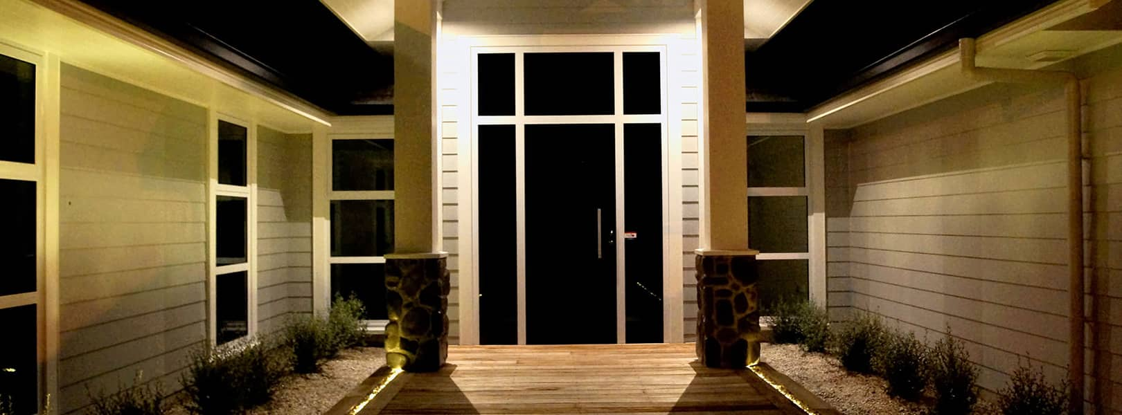 Indirect lighting effect from lights mounted behind two columns positioned either side of main door to a house. Light reflects from weatherboard wall.
