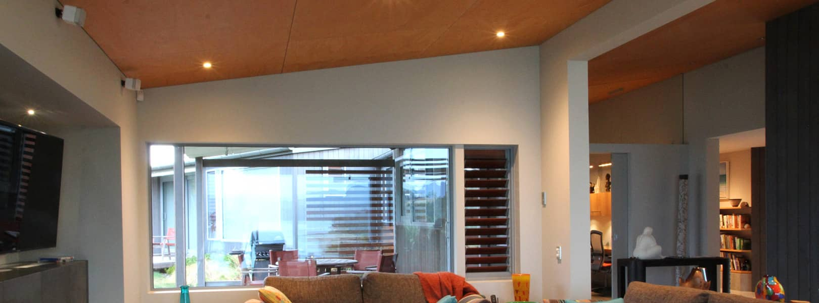 LED downlights recessed into modern sloping plywood ceiling in the lounge