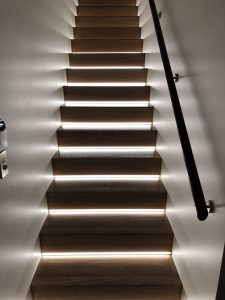 Staircase with handrail and lights recessed into stair risers